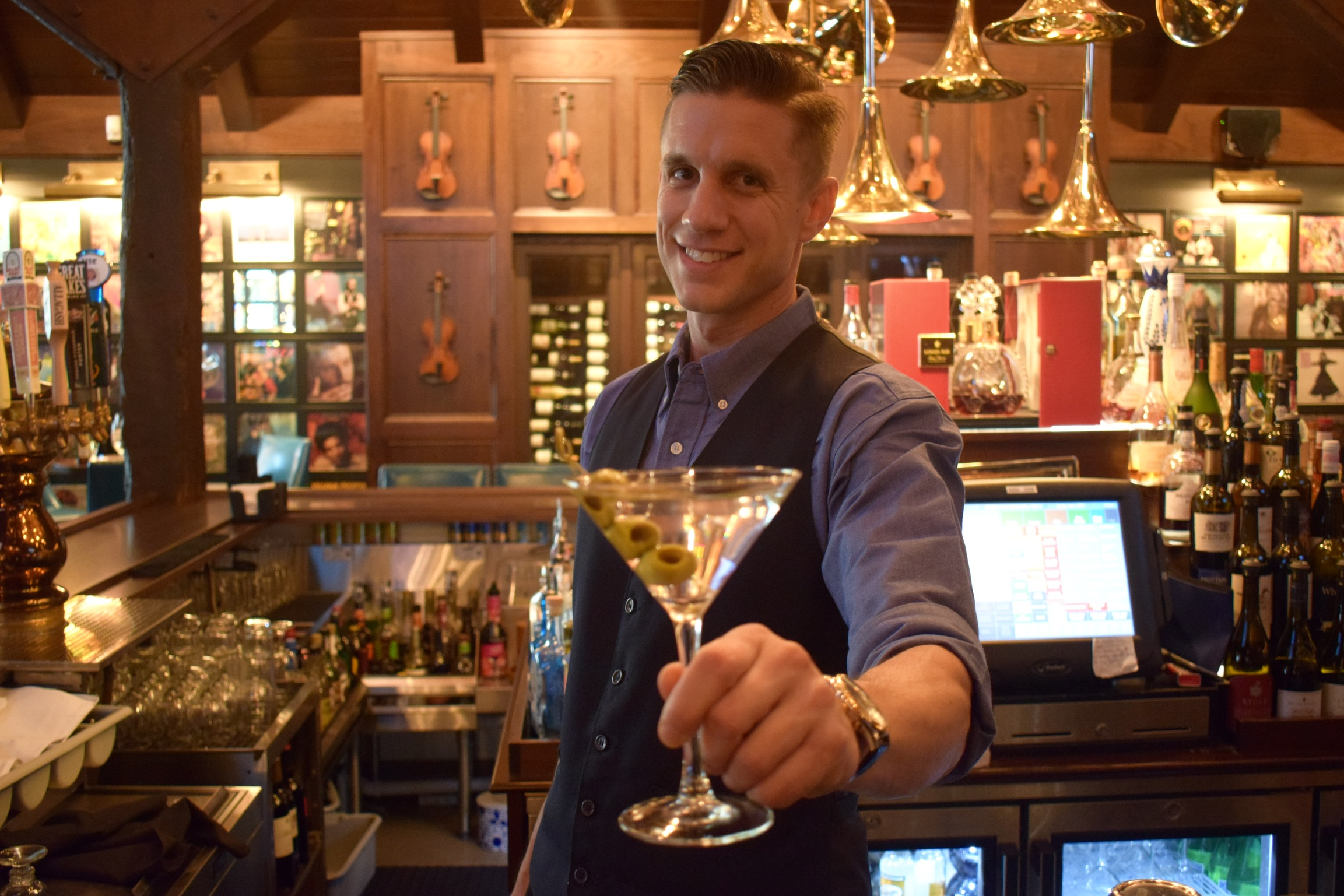 Friendly bartender serving a martini
